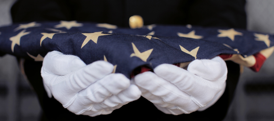 A military man holding out a folded American flag